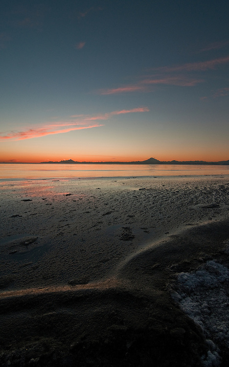 Alaska, Kenai, Cook Inlet. A tide change occurs with the sun setting behind Mount Redoubt and Mount Iliamna on the beach.