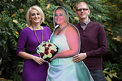 © licensed to London News Pictures. London, UK 13/11/2012. Claire Alsop and his husband Paul, posing with a cut-out from their wedding to show Claire's new shape as she slimmed down from 21st 9lb to a 10st 1½lb. Now she's been named Slimming World's Woman of the Year 2012. Photo credit: Tolga Akmen/LNP