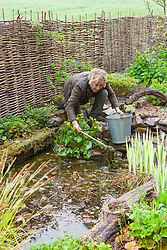 Carol Klein clearing weed from the pond