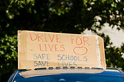 """24 JULY 2020 - DES MOINES, IOWA: A sign on the roof of a teacher's car in the motorcade around the Iowa State Capitol. Hundreds of teachers from across Iowa came to the state capitol Friday to protest Governor Kim Reynolds' order that school must reopen with in person education and minimized the potential for """"distance learning."""" The event was one of the largest COVID-19 protests in Iowa since the pandemic started, more than 740 teachers signed up to attend the protest. After the protest officially ended, many teachers left the capitol and drove to Gov. Reynolds' residence, where they drove around her mansion and honked horns. Some people left notes on the entrance to the governor's residence. Gov. Reynolds ordered the school reopening last week, but according to teachers, the state has not implemented health guidelines or bought protective equipment like face masks in the quantity required to slow the spread of the Coronavirus (SARS-CoV-2). Iowa's numbers of COVID-19 infections are up statewide.         PHOTO BY JACK KURTZ"""