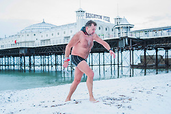 © Licensed to London News Pictures. 27/02/2018. Brighton, UK. Members of the Brighton Swimming Club brave the snow and cold sea water to take part in their daily swim. The water temperature today in Brighton and Hove dropped to 4C. Photo credit: Hugo Michiels/LNP