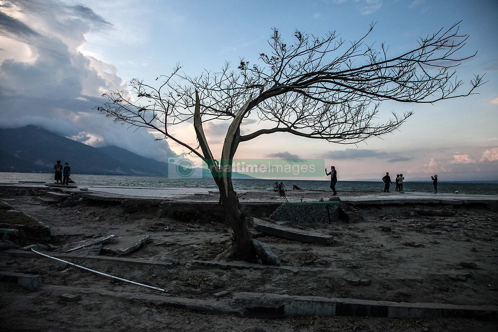 October 2, 2018 - Palu, Central Sulawesi, Indonesia - People on the beach beside a lone standing tree in Palu, after magnitude 7.5 earthquake and tsunami hit the area on September 28. The Indonesian government on October 2 said the death toll from a devastating quake-tsunami on the island of Sulawesi had risen to 1,234 confirmed dead. Emergency services fear that the death toll could rise into the thousands as rescue teams made contact with the nearby cities of Donggala and Mamuju and strong aftershocks continue to rock the city. (Credit Image: © Ivan Damanik/ZUMA Wire)