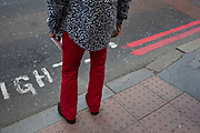 Man wearing red trousers and a flowery shirt interacting with his surroundings in London, England, United Kingdom. Red trousers if a fashion statement often associated with wealthy people.