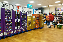 © Licensed to London News Pictures. 14/10/2021. London, UK. Shoppers walk past a display of chocolate Christmas selection boxes in Asda, north London, amid fears of chocolate shortage. Retail leaders warn that families should start to shop for Christmas now, amid fears that there may be shortage of presents, food, toys, electrical goods and other products, due to a shortage of HGV lorry drivers. Photo credit: Dinendra Haria/LNP