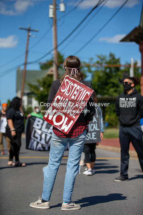 """A Black Lives Matter protester wears a sign reading """"systemic change now"""" at a rally outside of the police station in Milton, Pennsylvania on September 20, 2020. (Photo by Paul Weaver)"""