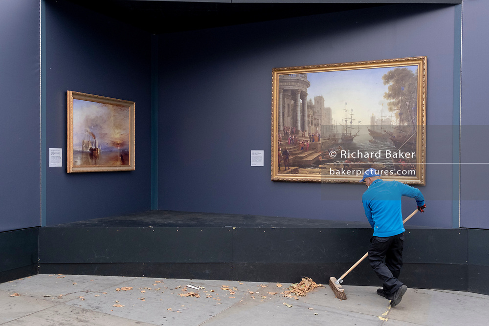 A street sweeper brushes leaves from beneath a copy of 'Seaport with the Embarkation of Saint Ursula' by Claude Lorrain (1641), part of a temporary display of historical art placed outside the National Gallery to show passers-by what can be seen in their galleries, on 1st September 2021, in Trafalgar Square, London, England.