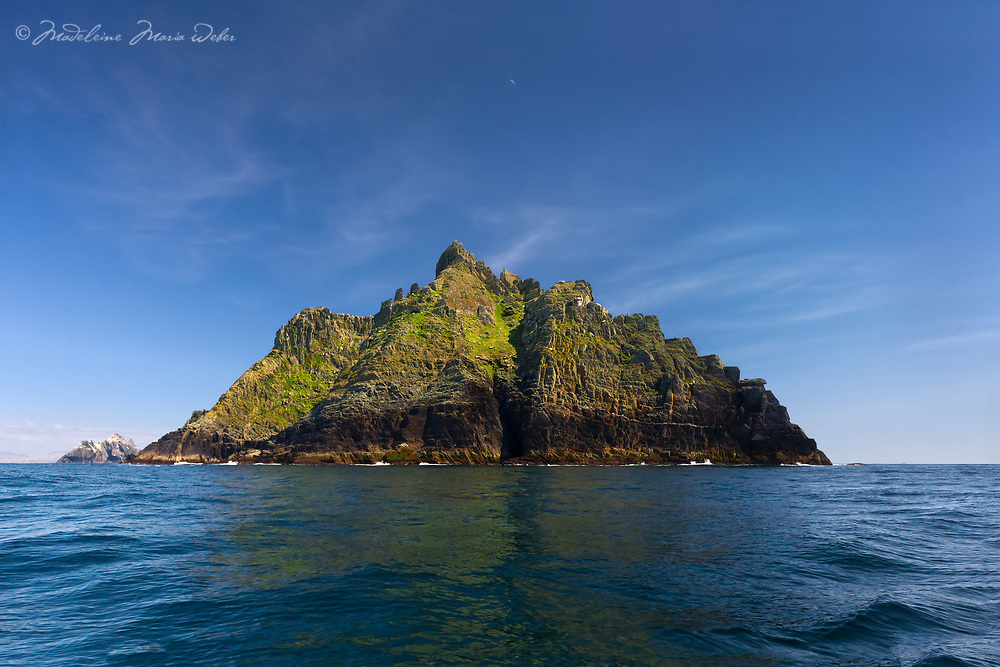 Skellig Michael from the sea with the Old Lighthouse and the South Peak and a clear blue sky day with a reflexion on the calm Atlantic sea, County Kerry, Skellig Coast, Skellig Ring, Ireland.<br /> <br /> DEUTSCH: Skellig Michael, der alte Leuchtturm und die Sued Spitze and einem Blauen-Himmel-Tag.<br /> <br /> ****** <br /> <br /> Visit & browse through my Photography & Art Gallery, located on the Wild Atlantic Way & Skellig Ring between Waterville and Ballinskelligs (Skellig Coast R567), only 3 minutes from the main Ring of Kerry road.<br /> https://goo.gl/maps/syg6bd3KQtw<br /> <br /> ******<br /> <br /> Contact: 085 7803273 from an Irish mobile phone or +353 85 7803273 from an international mobile phone