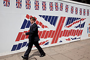 Man walks past a Union Jack flag hoarding covering a site in central London, UK. The sight of flags around the city has become more and more prominent as nationalism / patriotism takes hold around the time of the 2012 Olmpic Games.