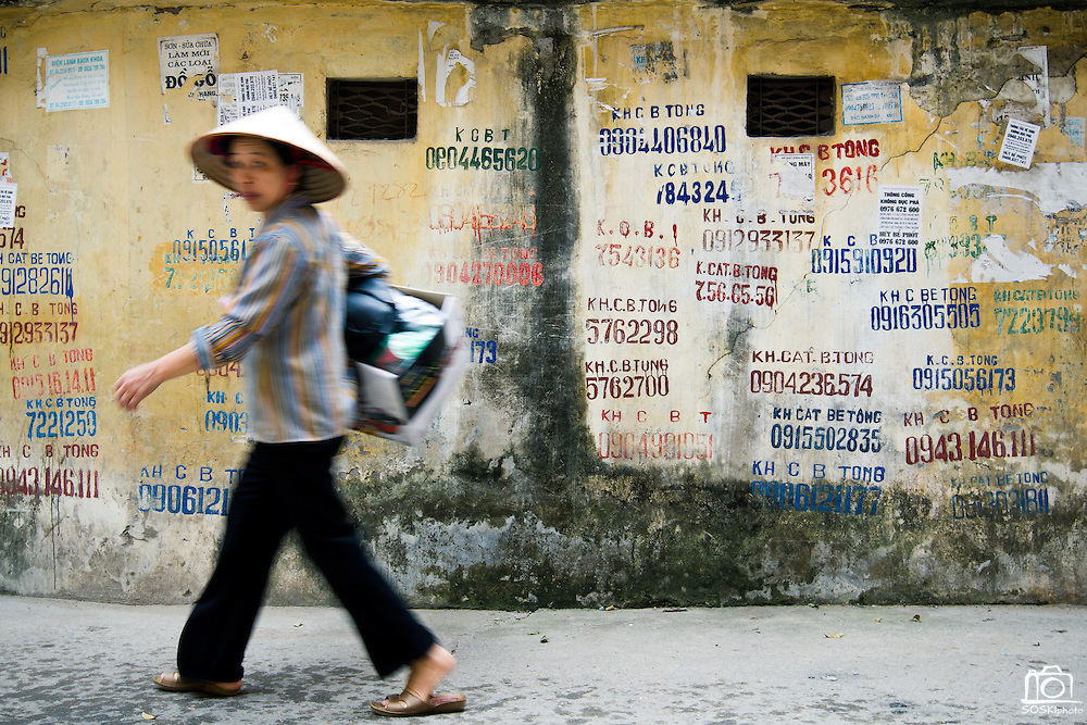 A woman walks through an alley in Hanoi, Vietnam.  Contractors looking for work risk fines by painting their phone numbers on walls.  Photo by Stan Olszewski/SOSKIphoto