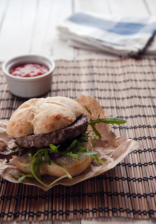 Lamb burger with cheese bun and rocket salad.