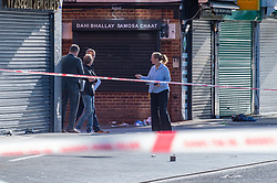 © Licensed to London News Pictures. 23/09/2019. London, UK. Police investigators look over the scene where a man in his 20's was found injured outside a shop in The Broadway, Southall. The man was taken to hospital suffering from a stab injury; he we was pronounced dead at 05:26 BST. Photo credit: Peter Manning/LNP