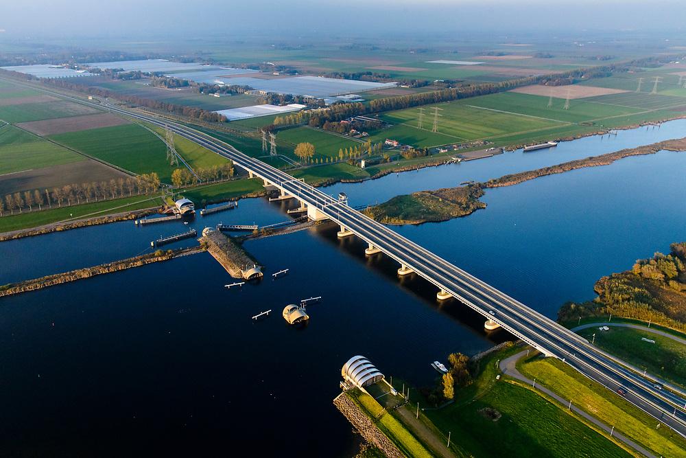 Nederland, Flevoland, Overijssel, Noordoostpolder, 04-11-2018. Ramspolbrug met N50, over de vaargeul het Ramsdiep. Naast de brug de balgstuw, onderdeel van Waterkering Kampen, tussen Ketelmeer en Zwarte Water (voorgeond). De balgstuw is een stormvloedkering en bestaat uit een opblaasbare dam of dijk, opgebouwd uit drie balgen. In niet-opgeblazen toestand liggen de balgen op de bodem. <br /> Ramspol bridge and Ramspol barrier, inflatable dike, between Ketelmeer and Black Water. The Balgstuw (bellow barrier) is a storm barrier and consists of an inflatable dam or dyke, composed of three bellows. Usually, each bellow rests on the bottom of the water.<br /> luchtfoto (toeslag op standaard tarieven);<br /> aerial photo (additional fee required);<br /> copyright© foto/photo Siebe Swart