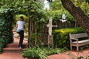 """A patron walks past """"Flying Folds"""" in the garden at Kay Contemporary Art in Santa Fe."""