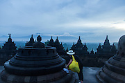 Tourist tying laces on statue of Buddha, Borobudur, Kedu Valley, South Central Java, Java, Indonesia, Southeast Asia