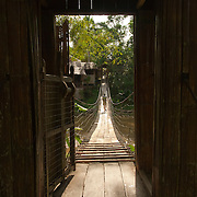 Wende Valentine crosses a bridge over the Penampang River outside of Kota Kinabalu, Sabah Province, Malaysia.