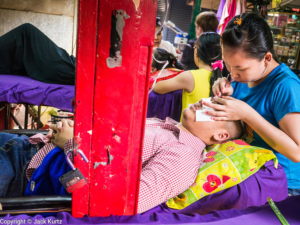 02 FEBRUARY 2013 - PHNOM PENH, CAMBODIA:  A man getshis eyebrows tweezed at a beauty parlor in a market in Phnom Penh, Cambodia.      PHOTO BY JACK KURTZ