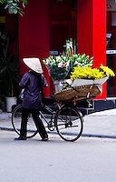 Flower sellers wearing conical hats in the old quarter of Hanoi wander the streets with baskets of colourful flowers.