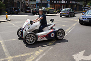 A hairdressers ATV GG Quadster, a 4-wheel motorbike, turns across a yellow grid across the junction at Herne Hill in south London, on 24th May 2019, in London, England.