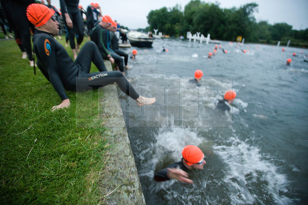 © Licensed to London News Pictures. 26/06/2011. Henley-on-Thames, UK. Competitors entering the water at the start line. Swimmers take part in the Henley Swim at dawn this morning (26/06/2011). The annual event sees competitors swim the length of the 2.1km course of the Henley Royal Regatta on the River Thames, after arriving in darkness, and walking half a mile to the start at sunrise. See special instructions. Photo credit should read: Ben Cawthra/LNP