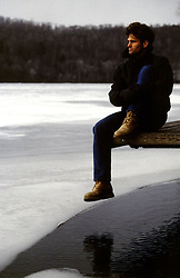 man sitting on a dock by a frozen lake