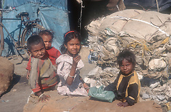 Group of young children sitting in front of makeshift tent in shanty town on outskirts of Gobindigarh; Punjab; India; next to bundles of cloth ready to be recycled,