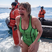 """A woman gasps after completing the """"polar plunge"""" in the icy waters off of Brown Bluff in Antarctica."""