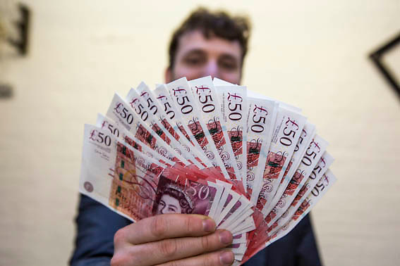 A man holding £50 notes