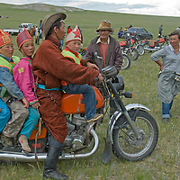 The Father of a young Naadam racer carries his son and friends on his motorcyle at finish line of 20km horse race at a remote pass in Arbulag Sum, near Muren in Hovsgol Aimag, Mongolia.