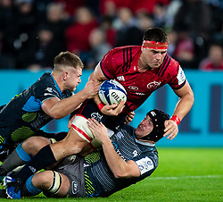 CJ Stander of Munster  is tackled by Morgan Morris of Ospreys<br /> <br /> Photographer Simon King/Replay Images<br /> <br /> European Rugby Champions Cup Round 1 - Ospreys v Munster - Saturday 16th November 2019 - Liberty Stadium - Swansea<br /> <br /> World Copyright © Replay Images . All rights reserved. info@replayimages.co.uk - http://replayimages.co.uk