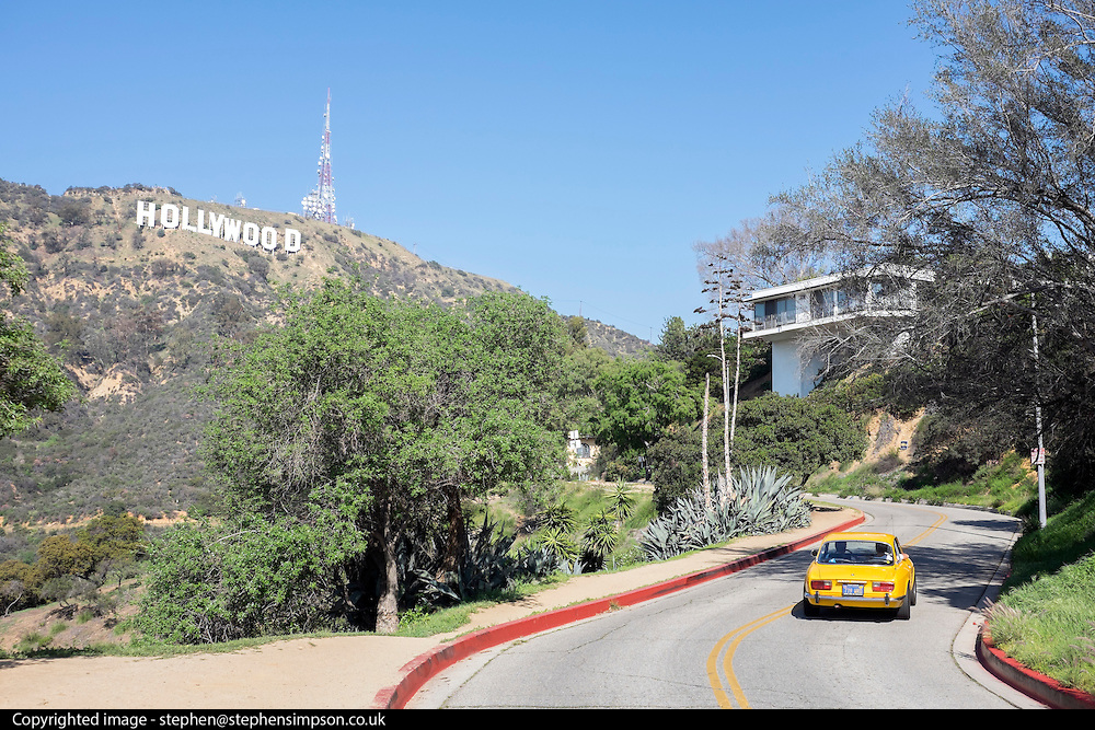 © Licensed to London News Pictures. 15/02/2015. Los Angeles, USA . A yellow car follows a road up near the Hollywood sign. Tourists photograph the Hollywood sign in Los Angeles, California. Photo credit : Stephen Simpson/LNP
