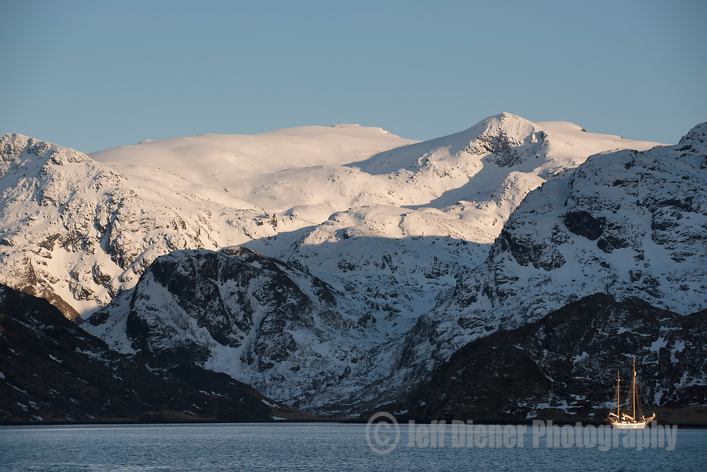 A large wooden sailboat anchors in last light in the Fjords of the Lyngen Alps, Norway.