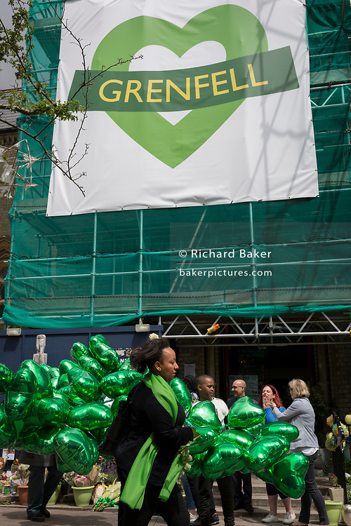 Green heart-shaped balloons during the memorial service for the Grenfell fire on the first anniversary of the tower block disaster, on 14th June 2018, in London, England. 72 people died when the tower block in the borough of Kensington & Chelsea were killed in what has been called the largest fire since WW2. The 24-storey Grenfell Tower block of public housing flats in North Kensington, West London, United Kingdom. It caused 72 deaths, out of the 293 people in the building, including 2 who escaped and died in hospital. Over 70 were injured and left traumatised. A 72-second national silence was held at midday, also observed across the country, including at government buildings, Parliament.