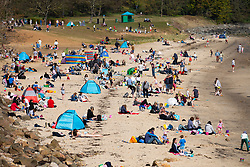 Aberdour, Scotland, UK. 17 April 2021.Unbroken sunshine and warm temperatures of 14C brought crowds of families to popular Silversands Beach in Aberdour, Fife.  The public were taking full advantage of the relaxation in travel restrictions in Scotland which came into effect on Friday.  An overflow car park was set up in a park to cope with the hundreds of cars that descended on the beach. Iain Masterton/Alamy Live News