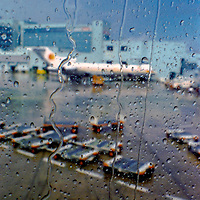 National Airlines Boeing 727 parked at a gate, Miami International Airport, 1973.  Image is taken through the window of a DC-10 aircraft just after a severe summer thunderstorm.