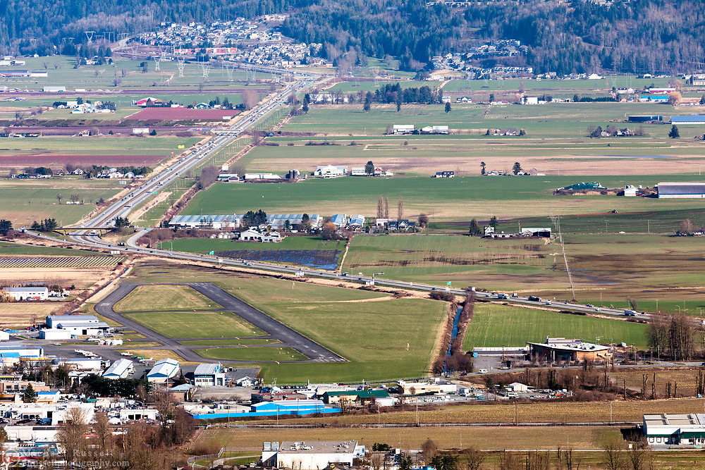 View of Chilliwack Municipal Airport (YCW) and the Trans Canada Highway in Chilliwack, British Columbia, Canada. The Trans Canada Highway (Highway 1) winds through the farmland next to the Chilliwack Airport during a late winter day.  Photographed from Hillkeep Regional Park on Chilliwack Mountain.