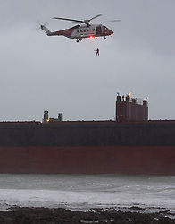 © Licensed to London News Pictures. 18/12/2018. Falmouth, UK. A member of a search and rescue hangs from a helicopter flying over Russian cargo ship Kuzuma Minin, run aground on the reef off Gyllyngvase beach in Falmouth Bay in the early hours this morning. The Falmouth lifeboat and the Coastguard helicopter are involved in the major incident.  Photo credit: Mark Hemsworth/LNP