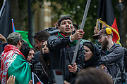 """A young demonstrator expresses a sad face as he carries and waves the Afghan national flag during a protest """"Save Afghanistan"""" against the Taliban resurgence rule outside Downing Street, Britain's PM Office in central London on Saturday, Aug 21, 2021. (VX Photo/ Vudi Xhymshiti)"""