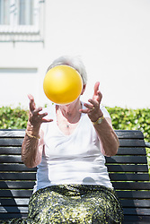 Senior woman exercising with ball at rest home garden, Bavaria, Germany, Europe