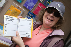 Woman holding up a large print diary,