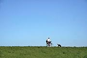 Nederland, Milliingen, 5-4-2020  Een moeder rijdt met een kind achterop haar fiets over de dijk. Hun hond loopt mee. Vanwege de coronadreiging wordt mensen gevraagd zoveel mogelijk binnen te blijven .Foto: Flip Franssen