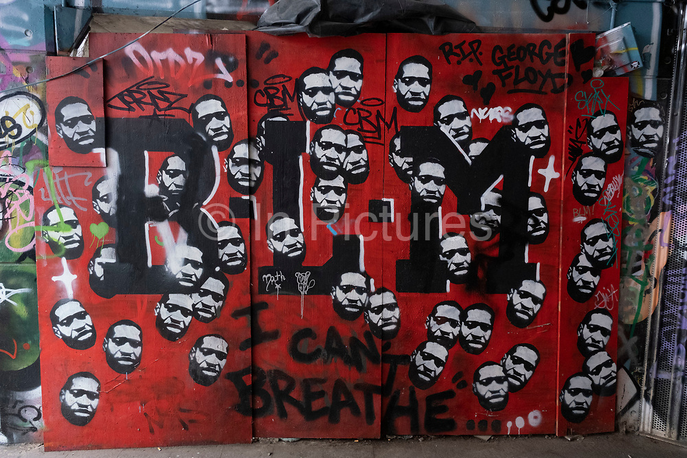 BLM Black Lives Matter spray painted street art graffiti depicting the face of George Floyd at the popular Leake Street Arches on 5th March 2021 in London, England, United Kingdom. Leake Street is a road tunnel in Lambeth, where graffiti is tolerated and encouraged regardless of the fact that it is against the law. The street is about 300 metres long, runs off York Road and under the platforms and tracks of Waterloo station.