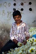 A boy threads marigolds for a garland at the Mehrauli flower market, Delhi, India