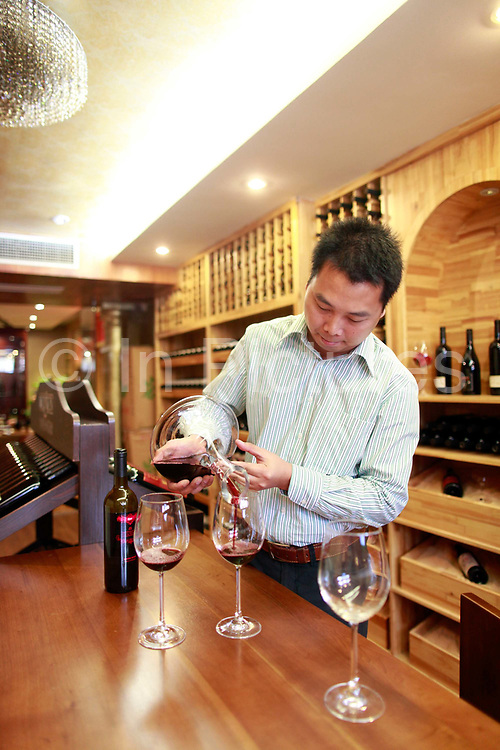 Lin Tiangui, a representative of Winston Wine, pours a glass of wine at one of its stores in Shanghai, China on 18 October, 2011. Photographer: Qilai Shen/BloombergLin Tiangui, a representative for Australia's Winston Wines Pty, pours a glass of wine at the company's store in Shanghai, China, on Tuesday, Oct. 18, 2011. Australian vineyards, facing slumping exports and rising competition, are turning to China as Chinese buyers creating surging demand among the nation's rich, who are developing a taste for wine and the expression of wealth and class it conveys.