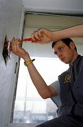 Trainee electrician doing repair work in council flat, London Borough of Haringey, UK