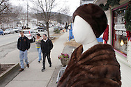Wurtsboro, New York  - A  manequin wearing a fur coat is on display in front of a consignment store as people walk on the sidewalk in the background during the Wurtsboro Winterfest on Feb. 11, 2012. ©Tom Bushey / The Image Works
