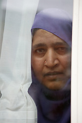 South Asian woman looking out of window,