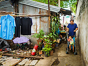 07 APRIL 2017 - BANGKOK, THAILAND:  A woman who lives in Pom Mahakan pushes her baby stroller down a pedestrian street in the old fort. The final evictions of the remaining families in Pom Mahakan, a slum community in a 19th century fort in Bangkok, have started. City officials are moving the residents out of the fort. NGOs and historic preservation organizations protested the city's action but city officials did not relent and started evicting the remaining families in early March.             PHOTO BY JACK KURTZ