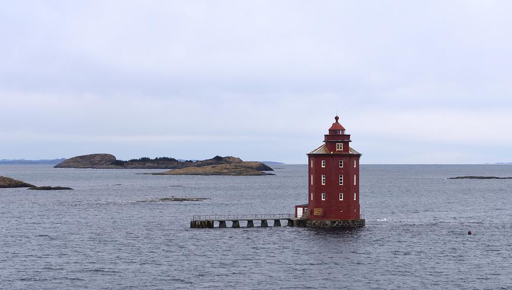 The red, octagonal  Kjeungskjær lighthouse, Kjeungskjær fyr seen from the Hurtigruten. Ørland, Sør-Trøndelag, Norway.