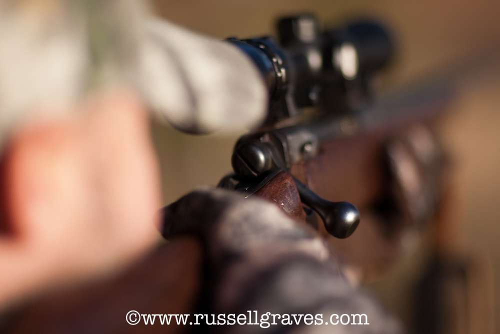 DEER HUNTER AIMING A .243 CALIBER RIFLE WITH A SCOPE