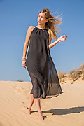 Woman in long black dress on the beach Model released